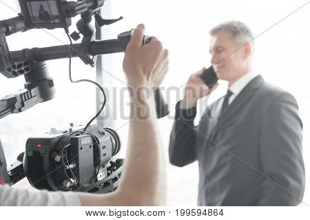 Videographer using steadycam making video of businessman talking on phone