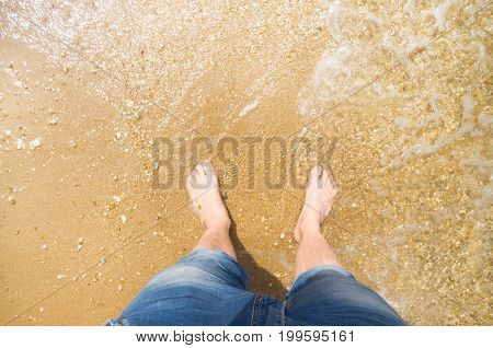 a man stands in the water on the beach