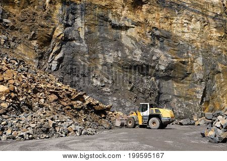 a wheel loader machine working on a large heap of stones in front of a rock face at a quarry