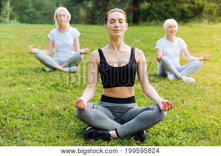 Feel your body. Delighted females crossing legs while meditating and putting hands on knees