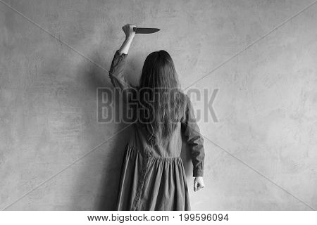 Evil woman with a knife. Her face is covered with hair. Retouched image and vignette is added.