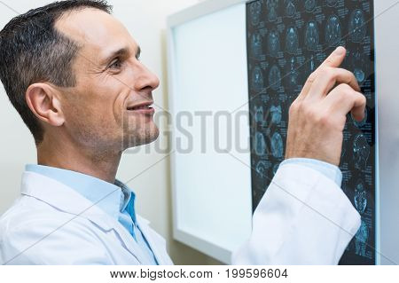 Careful analysis. The close up of a pleasant middle-aged male doctor carefully studying the results of computer tomography and pointing at them with a finger