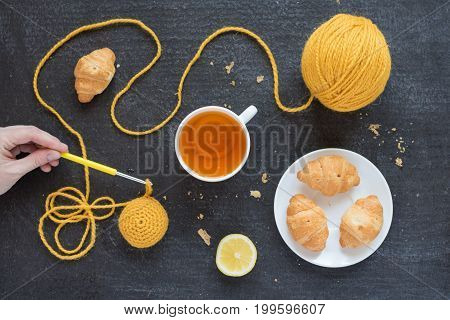 Lemon tea, yellow crocheting and croissants on a plate. Female hand is holding a crocheting hook.