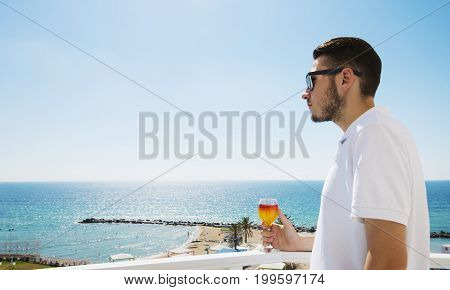 Man With Fruit Juice In Glass In Hand On Sea Background.