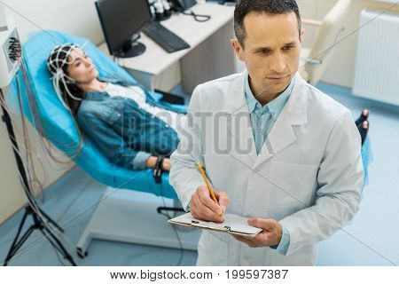 Best doctor. Pleasant concentrated doctor pondering medical condition of his female patient and making notes while she undergoing electroencephalography in the background