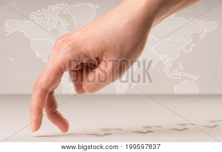 Female fingers walking with footsteps behind them and a world map in the background