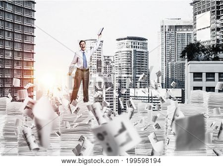 Businessman keeping hand with book up while standing among flying papers with cityscape and sunlight on background. Mixed media.