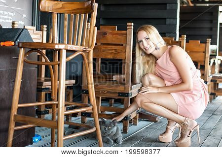 Beautiful fashion girl wearing pink dress high heeled shoes Stroking a cat in cafe