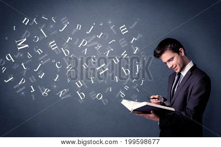 Casual young man holding book with white letters flying out of it