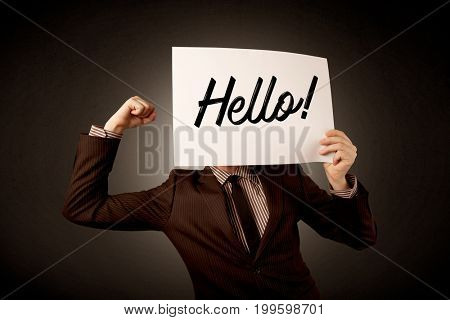 Young businessman hiding behind a greeting drawn on paper
