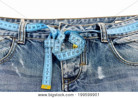 Top part of denim trousers isolated on white background. Close up of jeans with measure tape around waist. Healthy lifestyle and dieting concept. Blue jeans with yellow measure tape instead of belt.