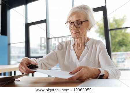 Work with documents. Joyful positive elderly woman holding a stapler and using it while joining pages of documents