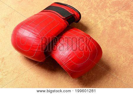 Sport Equipment On Orange Paper Background. Boxing Gloves