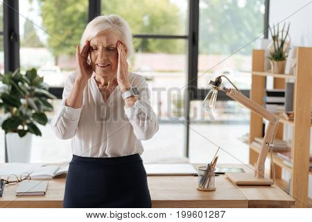 Awful headache. Sad professional elderly businesswoman standing in the middle of the office and holding her head while suffering from migraine