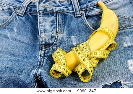 Health and male sexuality concept. Banana wrapped with yellow measure tape on jeans selective focus. Jeans zipper and pocket close up. Mens denim pants crotch with banana imitating male genitals.