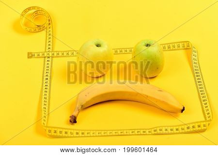 Square made of tape for measuring and disappointed face made of fruit inside it on bright yellow background. Concept of emotions and diet regime