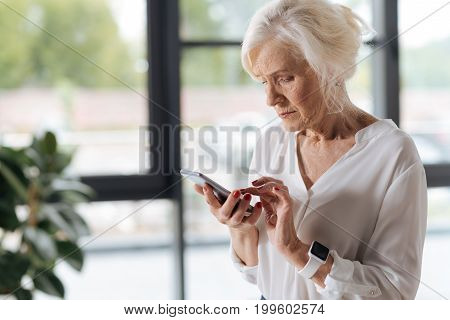 Modern smartphone. Nice pleasant elderly woman holding a smartphone and looking at its screen while pressing a button