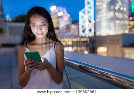 Woman using mobile phone in Hong Kong city