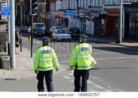 London March 2017 - Two officers from the Metropolitan Police patrol outside Clapham Junction Railway station in South West London.