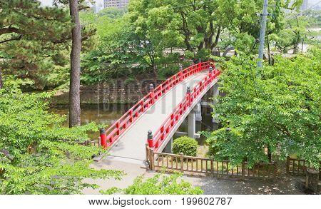 OKAZAKI JAPAN - MAY 31 2017: Red bridge over the moat of Okazaki Castle Japan. Castle was founded in 1455 by Saigo Tsugiyori shogun Tokugawa Ieyasu was born here in 1543