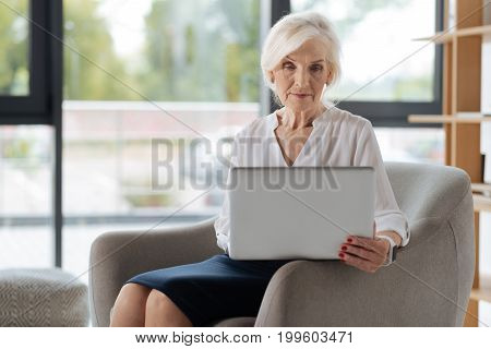 Comfortable workplace. Smart experienced aged businesswoman sitting in the armchair and looking at the digital screen while working on the laptop