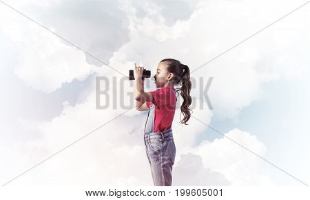 Little cute girl in overalls against sky background dreaming about future