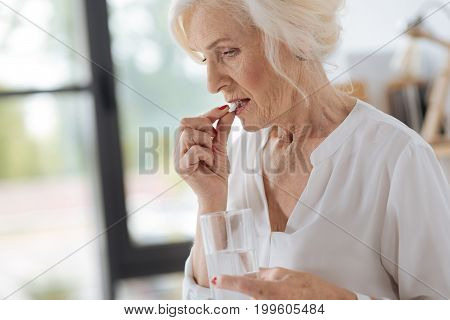 My dose. Sad cheerless elderly woman holding a glass of water and putting a pill to her mouth while feeling ill