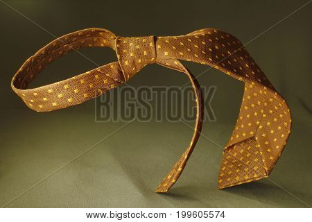 Brown With Yellow Spotted Necktie On Green Fabric Background, Fashion Accessory Close Up
