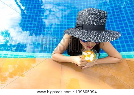 Lifestyle Woman in swimsuit relaxing and happy with cocktail on chaise-longue near swimming pool summer day. Summer Concept.