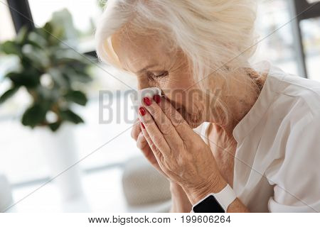 Seasonal disease. Nice moody aged woman sneezing and feeling not well while having a cold