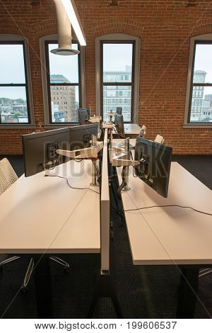 View of trendy modern open concept loft office space with big windows, natural light and a layout to encourage collaboration, creativity and innovation