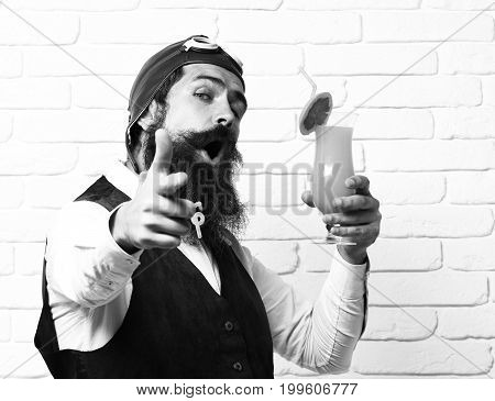 handsome bearded aviator man with long beard and mustache on satisfied face holding glass of alcoholic cocktail in vintage suede leather waistcoat with hat and glasses on white brick wall background