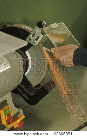 Manual Sharpening Of A Tool On Grinding Machine With Sparks Close Up