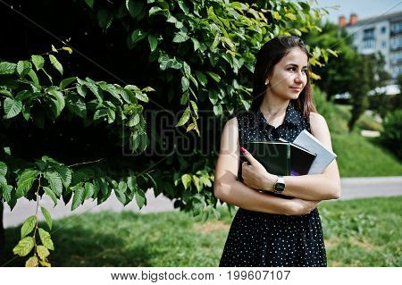 Portrait Of A Shy Young Woman In Black Polka Dot Dress Holding Books In The Park.