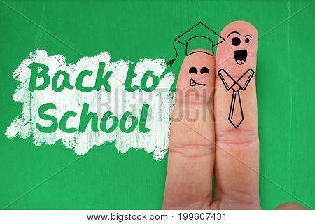 Digital anthropomorphic smiley faces of students on fingers against blackboard with copy space on wooden board