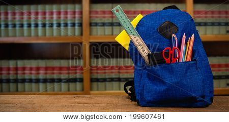 Schoolbag on wooden table against volumes of books on bookshelf in library