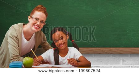 Happy pupil and teacher against greenboard on wall in school