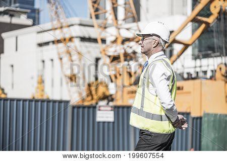 Engineer man in helmet and jacket controlling outdoor construction site