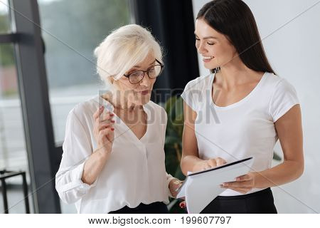This is interesting. Happy positive young woman standing with her senior colleague and pointing at the document while discussing work with her