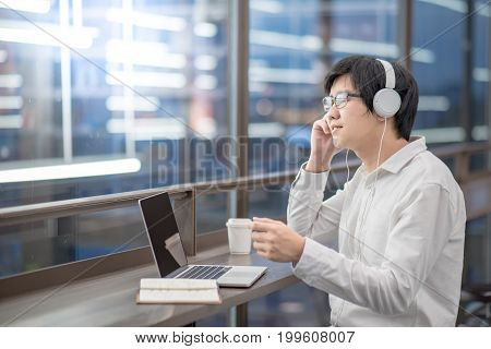Young Asian man dressed in casual style listening to music while working with his laptop. Digital nomad in co working space modern IT lifestyle with work life balance concept.