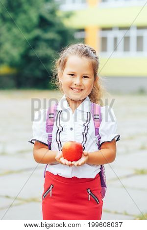 Cute Asian-looking girl holding an apple in the hand on a school background. The girl goes to school