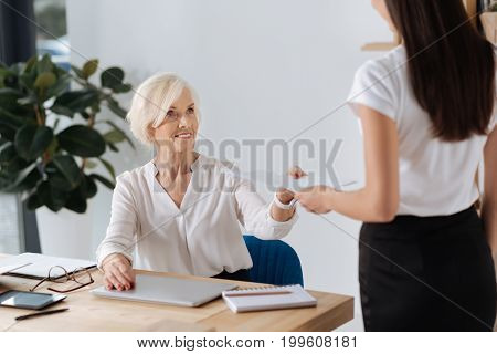Months report. Nice pleasant professional businesswoman sitting at the table and smiling while giving her secretary a document