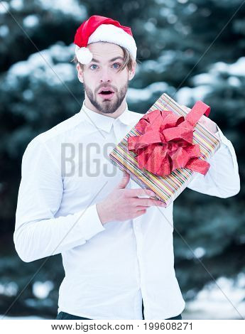handsome bearded surprised man or sexy christmas guy in red santa claus hat and shirt in winter outdoor at green fir tree with snow holds present box on natural background
