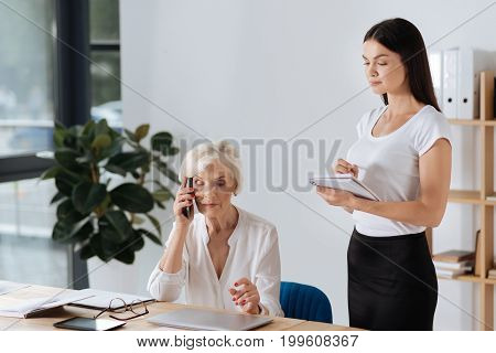Ready to write. Intelligent attentive young woman holding a notebook and being ready to take notes while listening to her boss