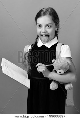 Girl Holds Teddy Bear And Open Notebook With Marker