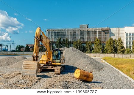 Tracked Excavator On A Construction Site Among Piles Of Crushed Stone