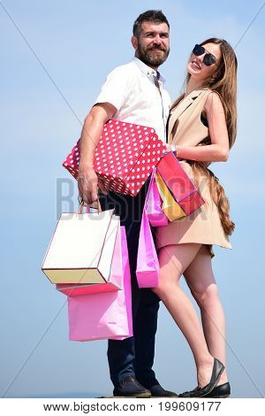 Couple carries pink packets and box on blue background. Sexy girl and guy with happy faces making purchases. Shopping and shopaholism concept. Man with beard and long haired woman hold shopping bags