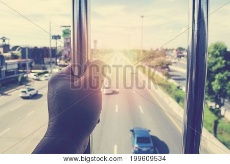 Man hand holding fence bar of overpass and blurry of cars on the road in background. Freedom or Imprison concept