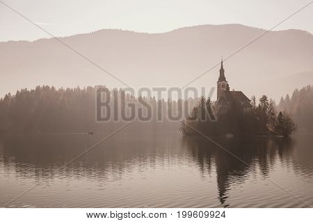 Amazing view on Bled Lake in fog. Mysterious view on Island with Catholic Church in the middle of the lake. Autumn Winter in Slovenia Europe.