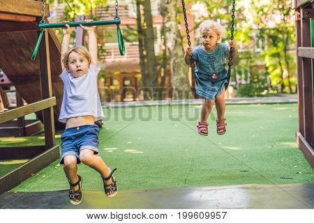 Boy And A Girl On Swings On Playground With Smile On Sunny Summer Day